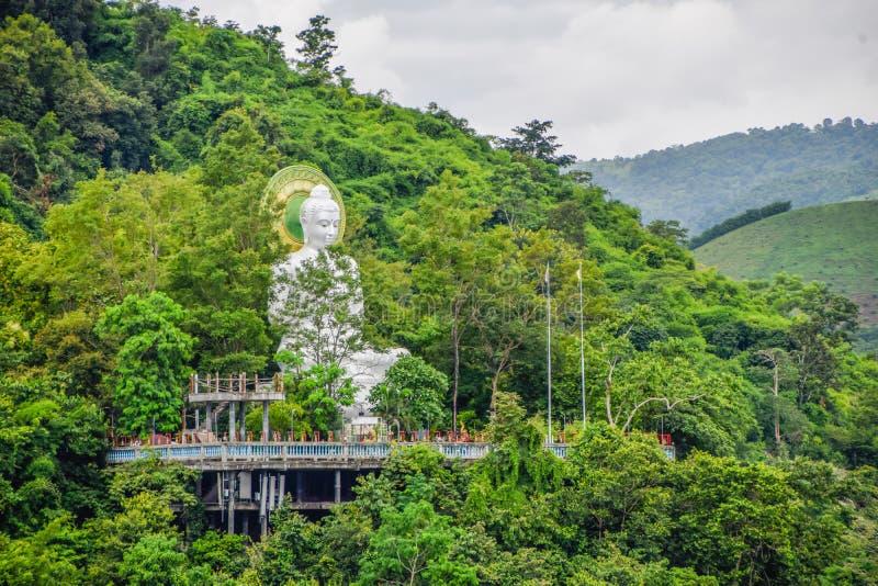 Un gran estudio blanco de Buda está consagrado en un patio de cemento en una zona montañosa rodeada de árboles verdes en Myanma imagen de archivo libre de regalías