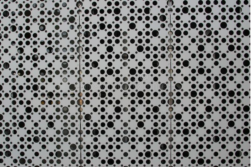 Un gran número de agujeros en una hoja del metal foto de archivo libre de regalías