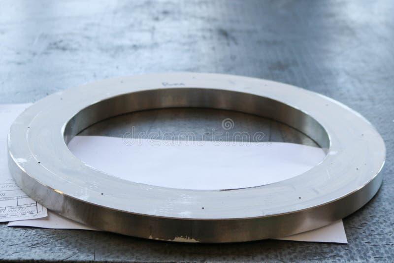 Un grand anneau brillant rond en métal avec de petits trous, trous, une bride sur la table fonctionnante de fer dans l'usine, l'a photos libres de droits