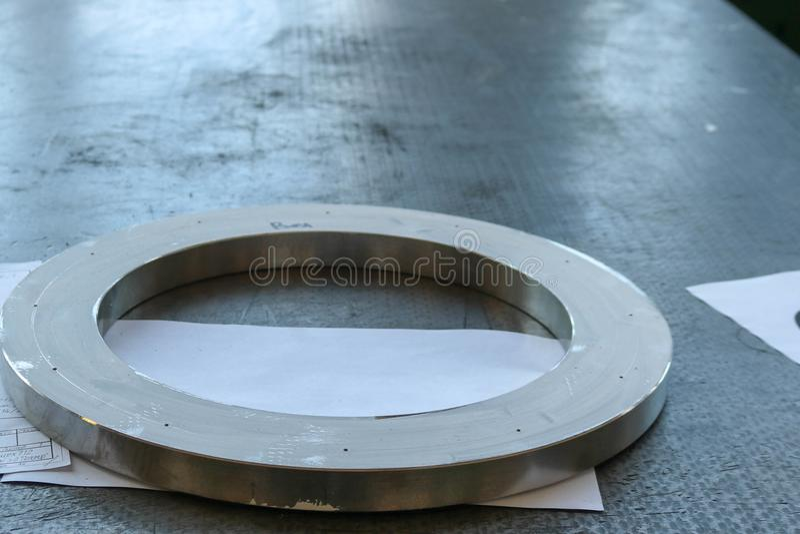 Un grand anneau brillant rond en métal, une bride sur une table fonctionnante de fer dans une usine, un atelier photos libres de droits