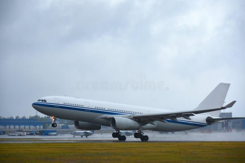 Un grand avion de passagers touche le train d'atterrissage en débarquant, en décollant à l'aéroport pendant la pluie photographie stock