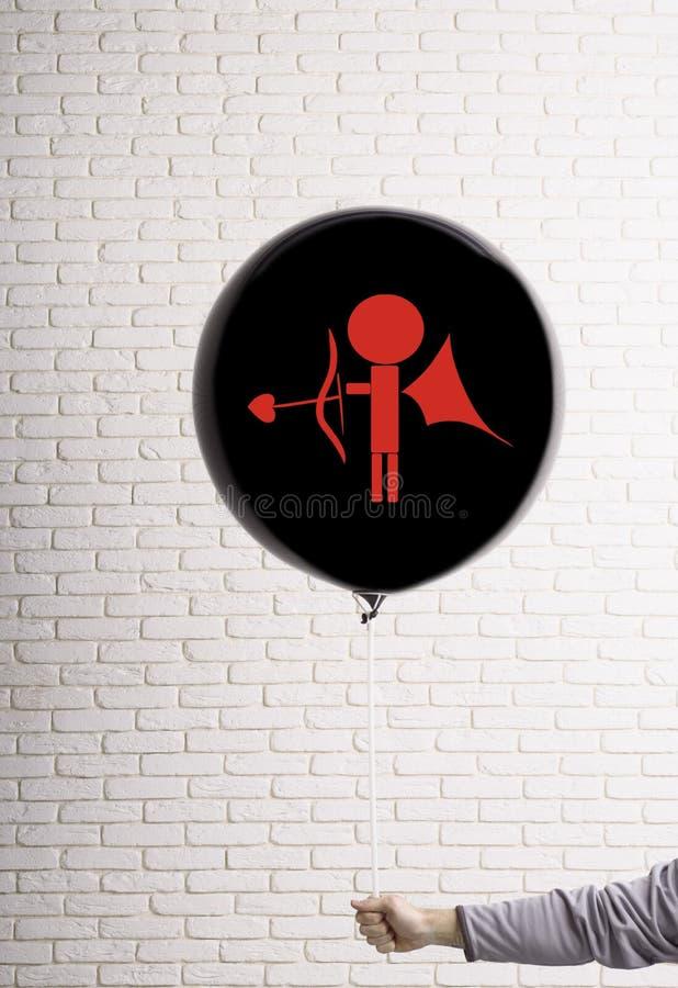 Un grand ballon noir dans la main sur laquelle un cupidon avec un tir à l'arc est dessiné Concept de jour du ` s de Valentine photographie stock