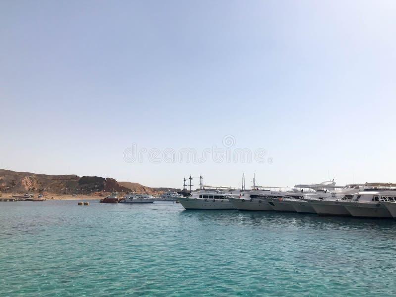 Un grand choix de moteur et de bateaux de navigation, bateaux, revêtements de croisière se tiennent sur un dock dans le port dans images libres de droits