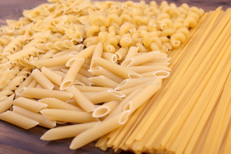 Un grand choix de types et de formes de pâtes sèches italiennes sur un fond en bois Pâtes crues, dures, crues et sèches Macaronis image stock