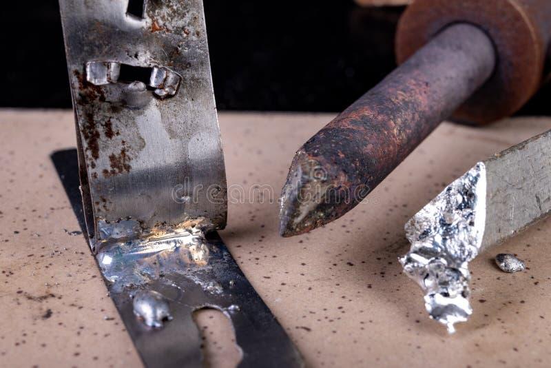Un grand fer à souder et des accessoires de soudure sur une table d'atelier Feuilles se reliantes utilisant la soudure image libre de droits