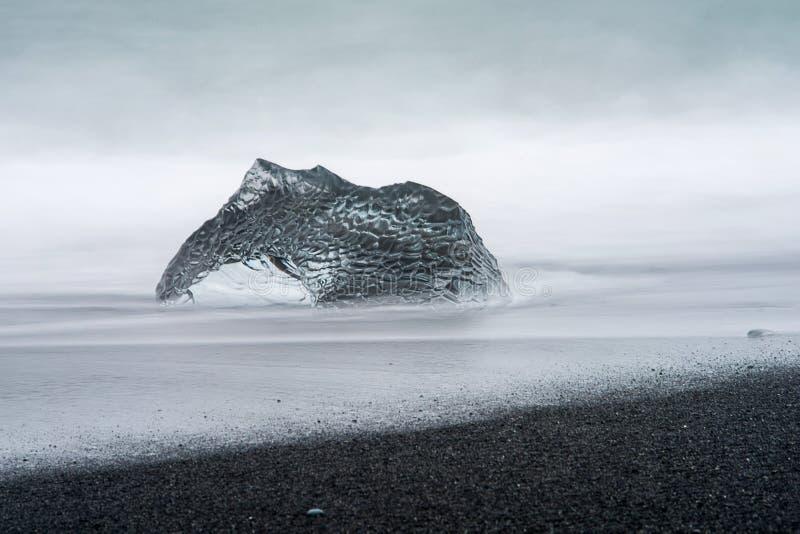 Un grand morceau abstrait de glace de glacier se repose sur une plage noire de sable en Islande images libres de droits