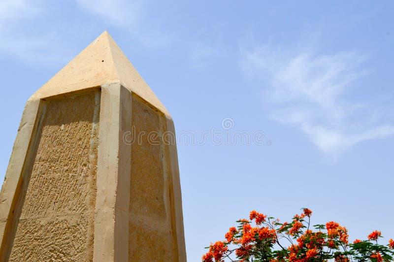 Un grand obélisque aigu fait en pierre jaune en Egypte contre un ciel bleu et des fleurs rouges photo stock