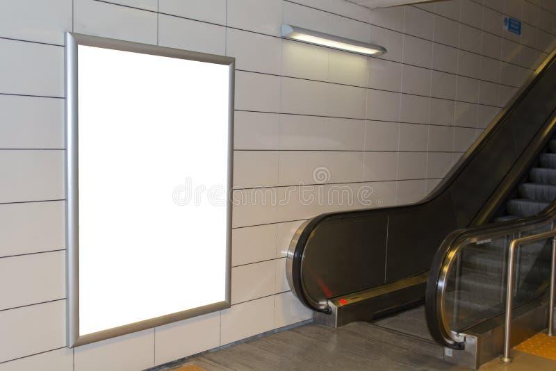 Un grand panneau d'affichage de blanc d'orientation de verticale/portrait avec le fond d'escalator photo libre de droits