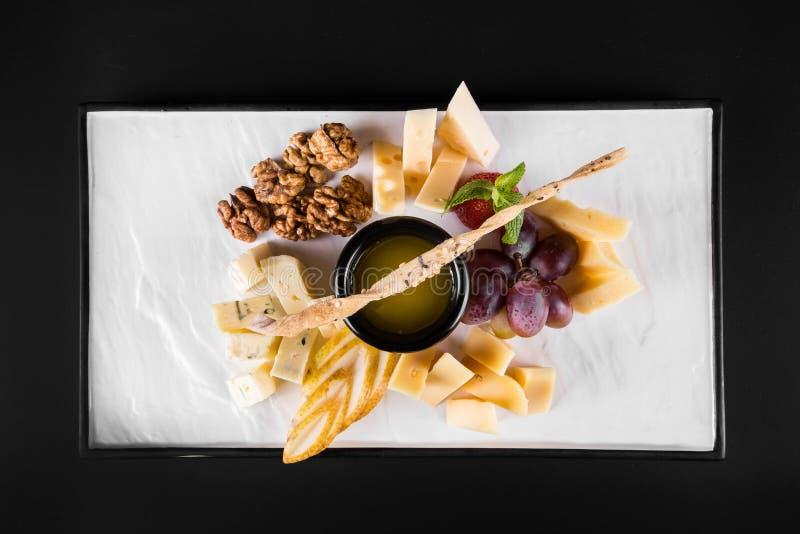 Un grand plat avec un large choix des casse-croûte aiment des raisins, fromage, les noix, biscuits sur le fond foncé Vue supérieu photo stock