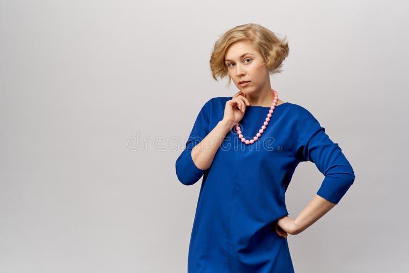 Un grand portrait fortement détaillé de studio d'une belle jeune femme blonde dans une robe bleue élégante photographie stock