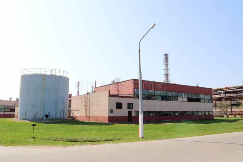 Un grand récipient gris en métal, un baril avec une trappe ouverte et un bâtiment rouge de production à un raffinerie de pétrole, photos stock