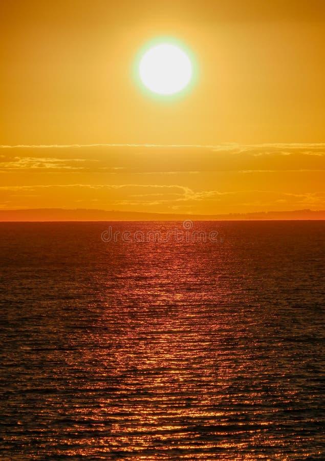 Un grand soleil lumineux d'été plaçant au-dessus de la mer photographie stock libre de droits