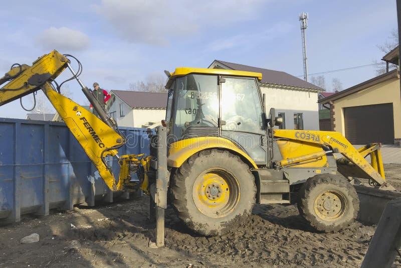 Un grand tracteur jaune charge des déchets de construction dans un conteneur avec un seau image stock