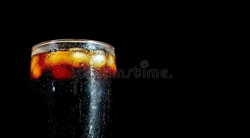Un grand verre de kola avec des glaçons d'isolement sur le noir photo libre de droits