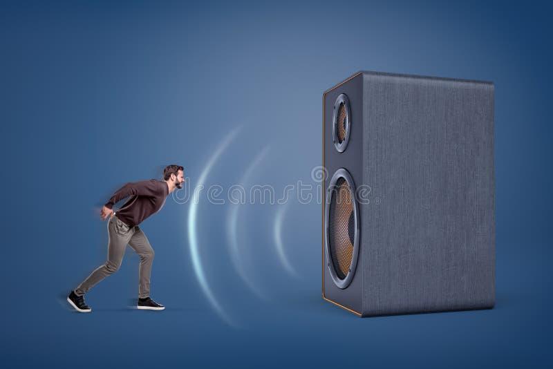 Un grande altoparlante d'annata emette le forti suono-onde e quasi spazza un piccolo uomo aggressivo fuori dai suoi piedi fotografia stock