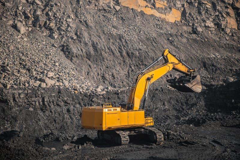 Un grande escavatore giallo con un secchio intero di carbone nero effettuerà il carico nella miniera aperta immagini stock libere da diritti