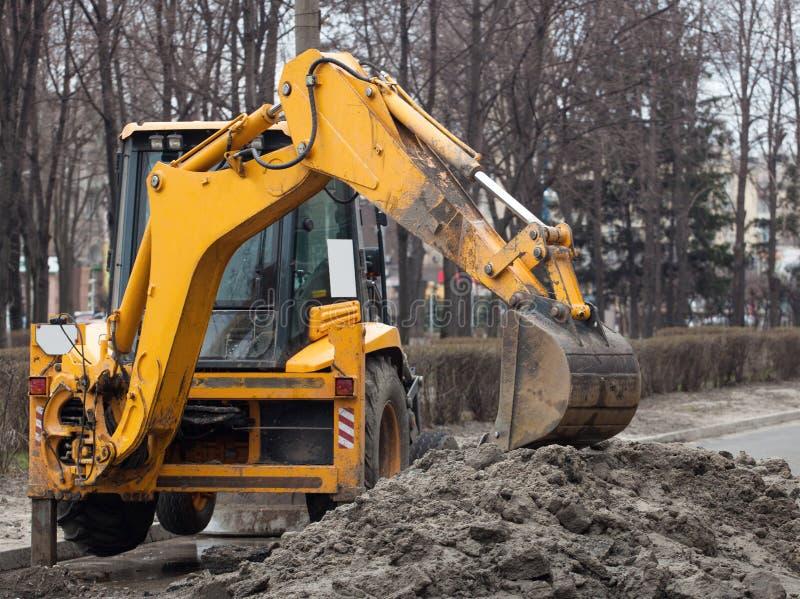 Un grande escavatore giallo sta in mezzo alla via vicino al foro scavato immagine stock