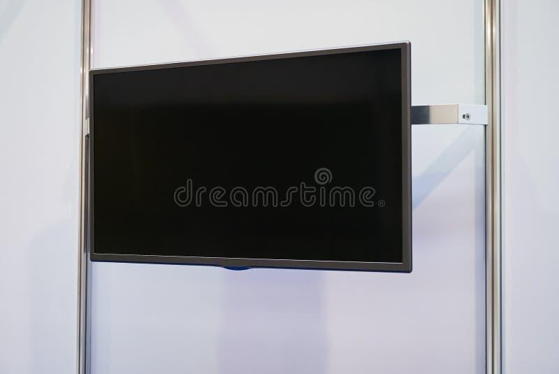 Un grande schermo del nero TV su una parete bianca fotografie stock