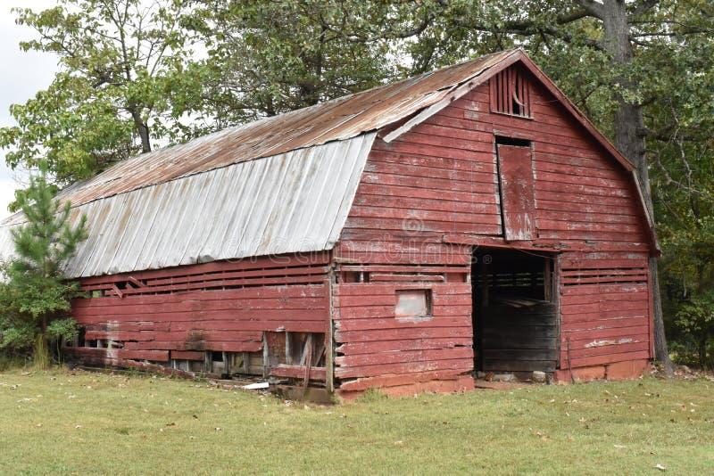 Un granero rojo dilapidado sobrevive en barrios residenciales periféricos fotografía de archivo