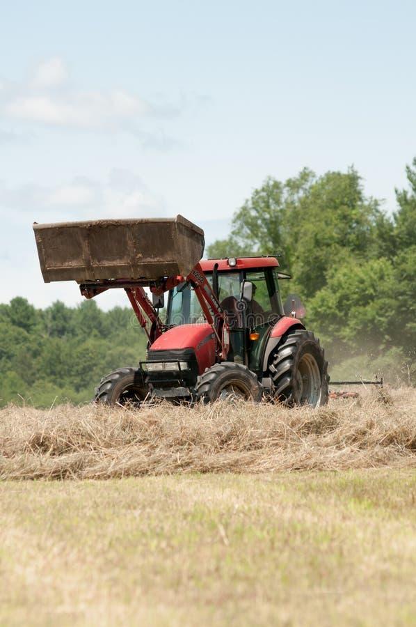 Un granjero en un tractor del rojo hace heno un campo en Nueva Inglaterra imágenes de archivo libres de regalías