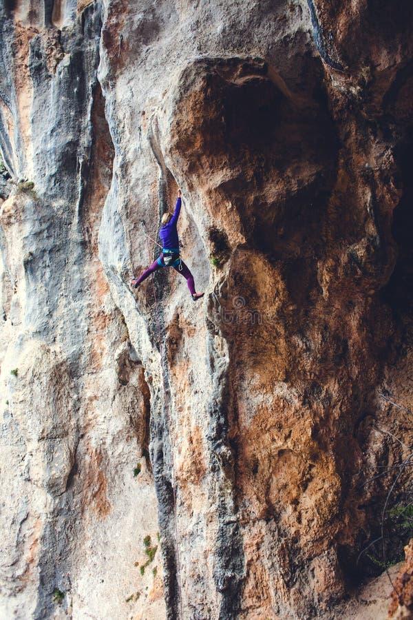 Un grimpeur de roche sur une roche photographie stock