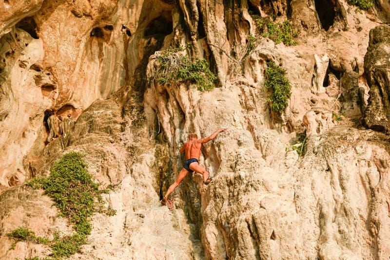 Un grimpeur solo libre d'homme supérieur accroche sur la falaise de Rai Leh photos stock