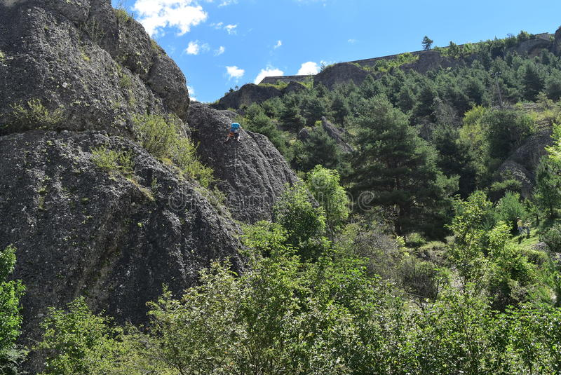 Un grimpeur sur une roche énorme image stock