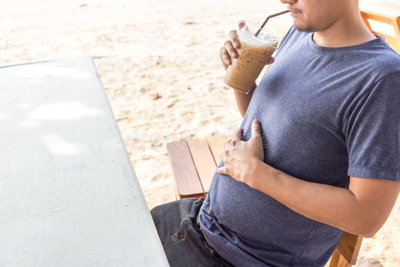 Un gros homme et un grand café de boissons de ventre sur la plage image stock