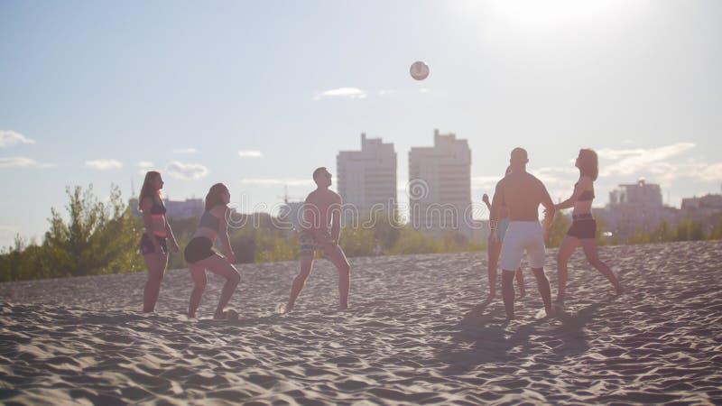Un groupe d'amis jouant le volleyball sur la plage contre un beau coucher du soleil photographie stock