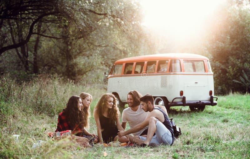 Un groupe d'amis s'asseyant sur la terre sur une promenade en voiture par la campagne, ayant le pique-nique photographie stock