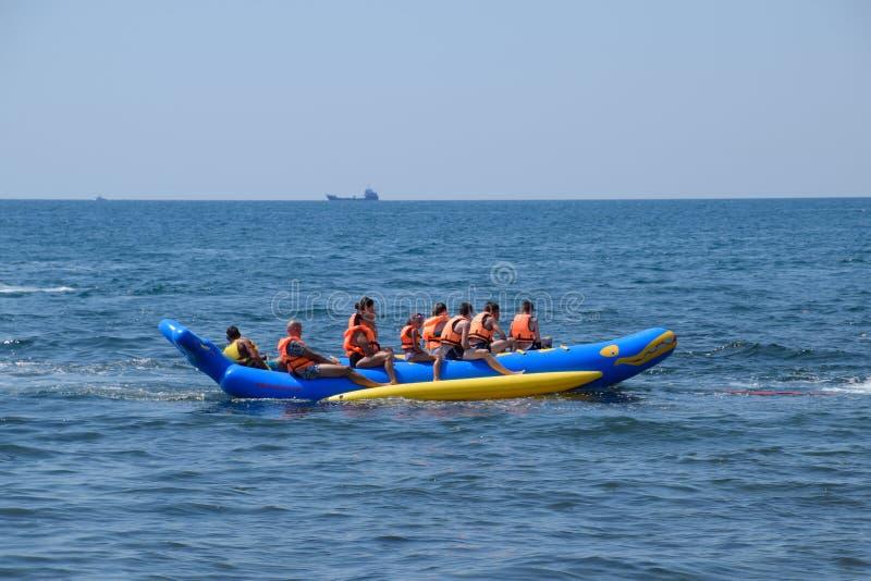 Un groupe d'enfants sur un bateau gonflable en mer Enfants dans des gilets de sauvetage images libres de droits