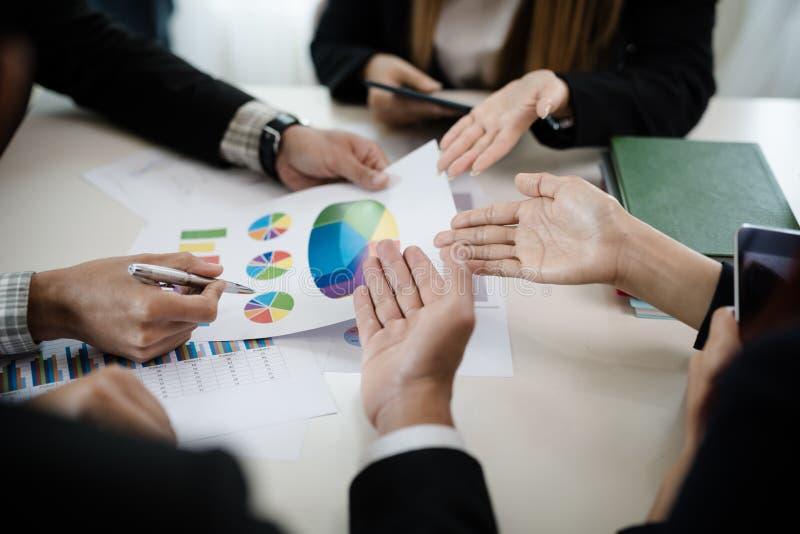 Un groupe d'hommes d'affaires et les femmes se réunissent ensemble pour voir le GR images stock
