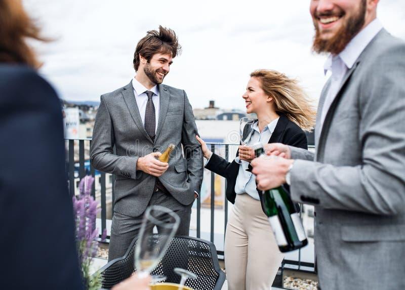 Un groupe d'hommes d'affaires joyeux ayant un ext?rieur de partie sur la terrasse de toit dans la ville photos stock
