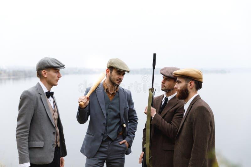 Un groupe de bandits dans les costumes et avec des armes discutent quelque chose rétro outdoors images libres de droits