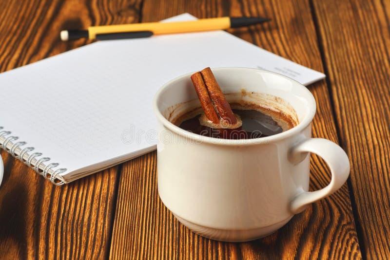 Un groupe de cannelle a tricot? avec une corde, une tasse de caf? et un carnet pour ?crire sur un plan rapproch? en bois de fond image stock