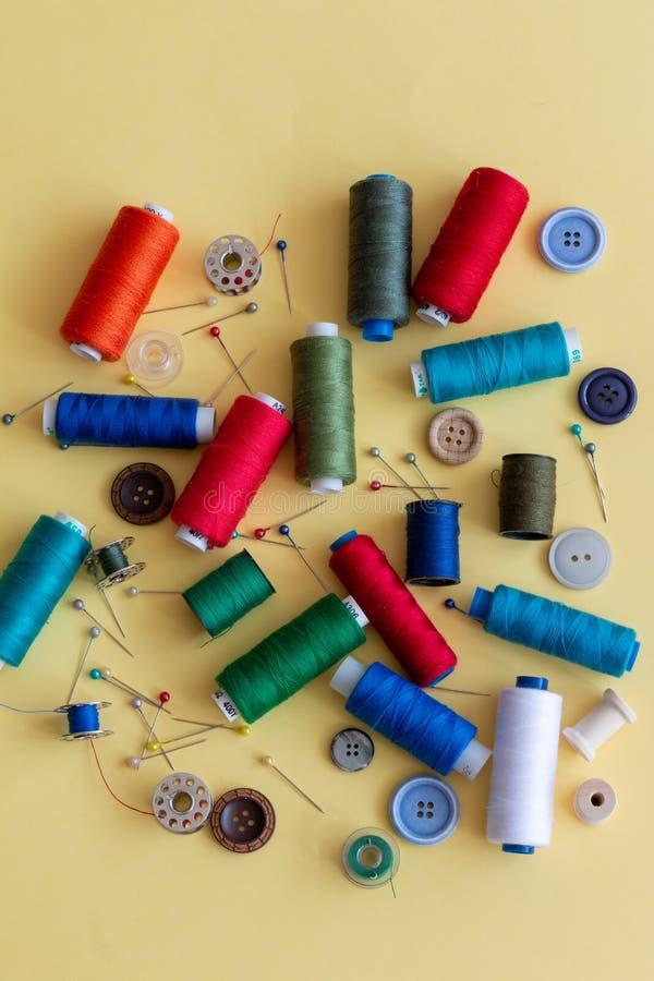 Un groupe de choses de couture colorées sur un fond jaune photographie stock