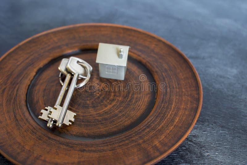 Un groupe de clés se trouvent d'un plat de cru, avec une imitation de la maison sous forme de disposition en métal image libre de droits