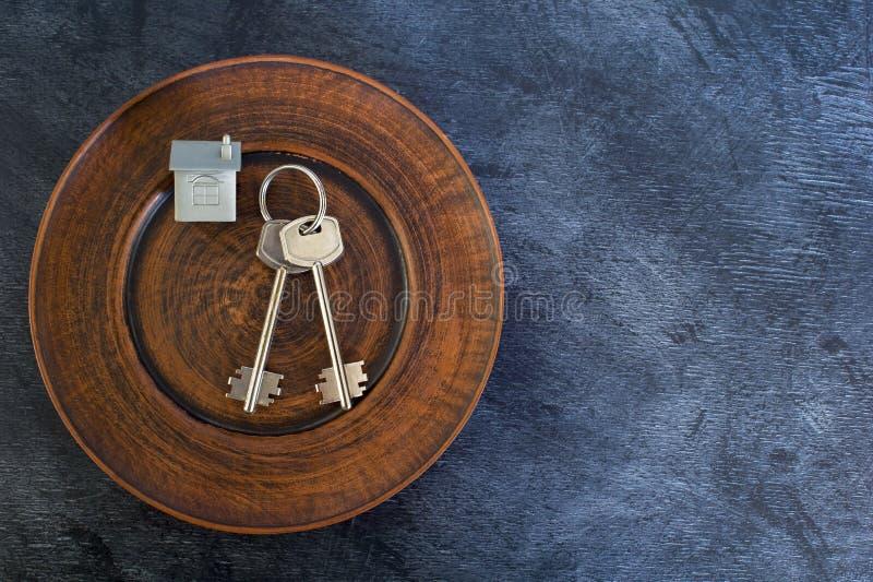Un groupe de clés se trouvent d'un plat de cru, avec une imitation de la maison sous forme de disposition en métal photo libre de droits