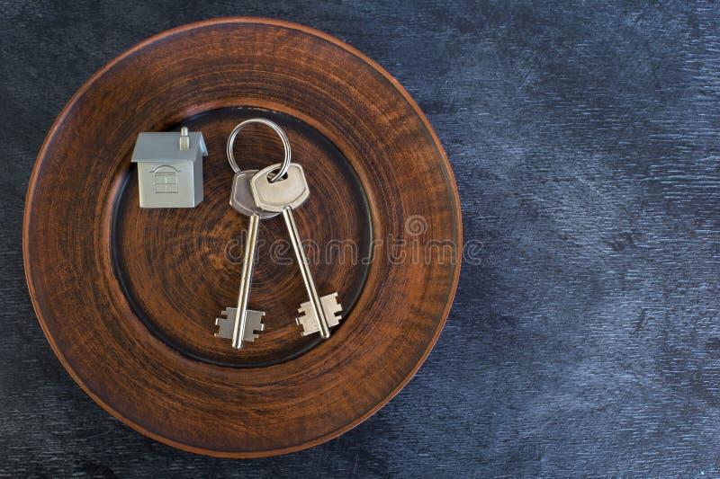 Un groupe de clés se trouvent d'un plat de cru, avec une imitation de la maison sous forme de disposition en métal photographie stock libre de droits