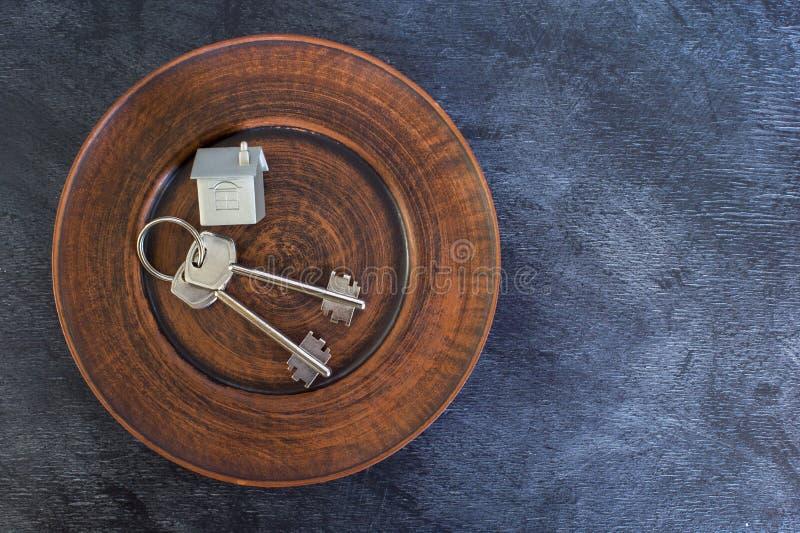 Un groupe de clés se trouvent d'un plat de cru, avec une imitation de la maison sous forme de disposition en métal images libres de droits