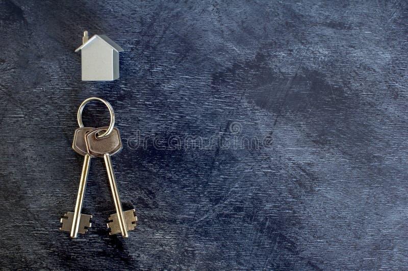 Un groupe de clés se trouvent sur un fond foncé de cru avec une imitation de la maison sous forme de disposition en métal images libres de droits