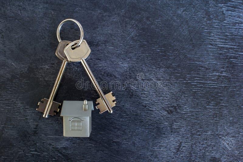 Un groupe de clés se trouvent sur un fond foncé de cru avec une imitation de la maison sous forme de disposition en métal photographie stock
