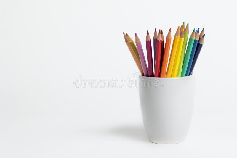Un groupe de couleur crayonne dans une tasse blanche photo stock