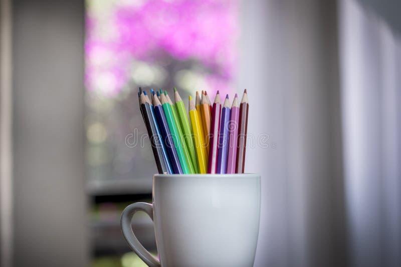 Un groupe de couleur crayonne dans une tasse blanche image stock