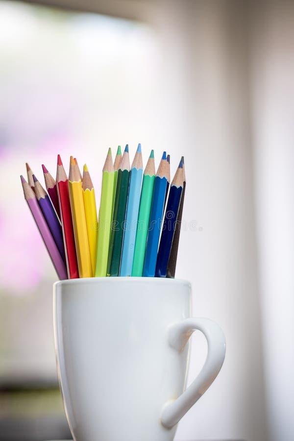 Un groupe de couleur crayonne dans une tasse blanche photographie stock libre de droits