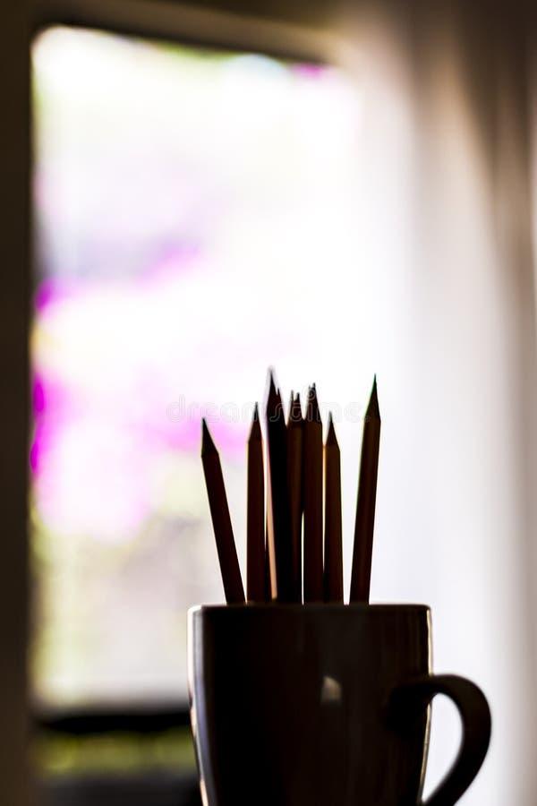 Un groupe de couleur crayonne former une silhouette dans une tasse blanche image libre de droits