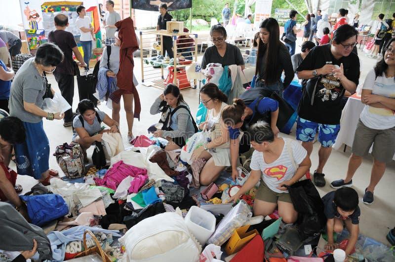 Un groupe de femmes asiatiques prenant des habillements à un marché gratuit photos stock