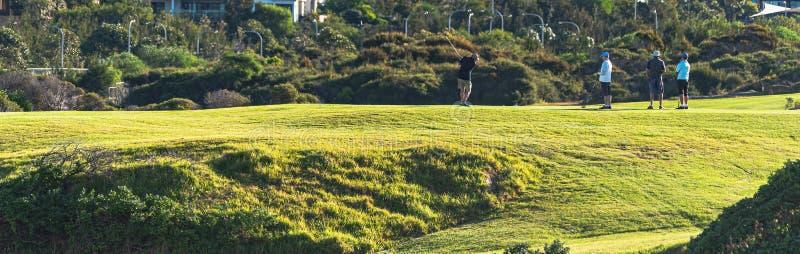 Un groupe de golfeurs frappant une boule au trou photos libres de droits