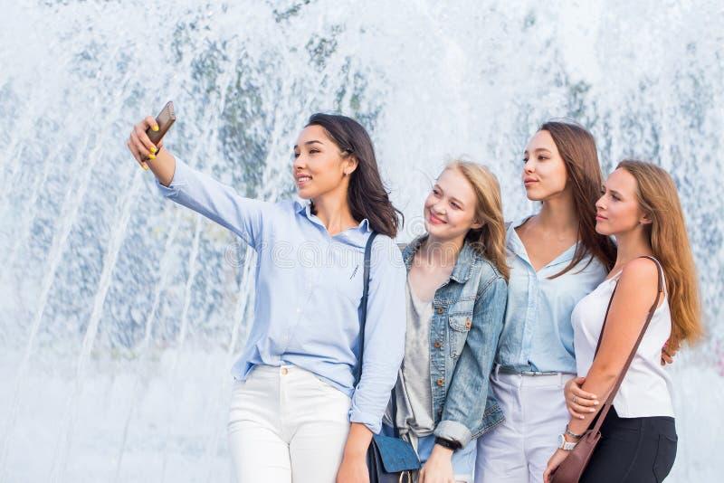 Un groupe de jeunes filles attirantes des étudiants prend un selfie sur le fond d'une belle fontaine photographie stock libre de droits
