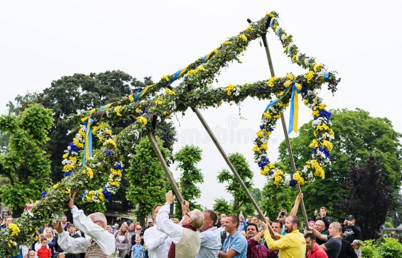 Un groupe de mâle offre travailler à soulever le mât d'une façon traditionnelle à une célébration de milieu de l'été dans Hagelby images stock